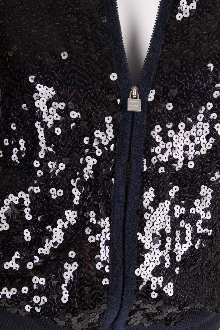 A dark blue sequin jacket from the Sports Line of Chanel, 2008 Cruise Collection. Fancy!!  Front and back are covered with sequins, terry cloth detailing on the sleeves and the area around the zipped pockets. A drawstring at the collar, in the waist
