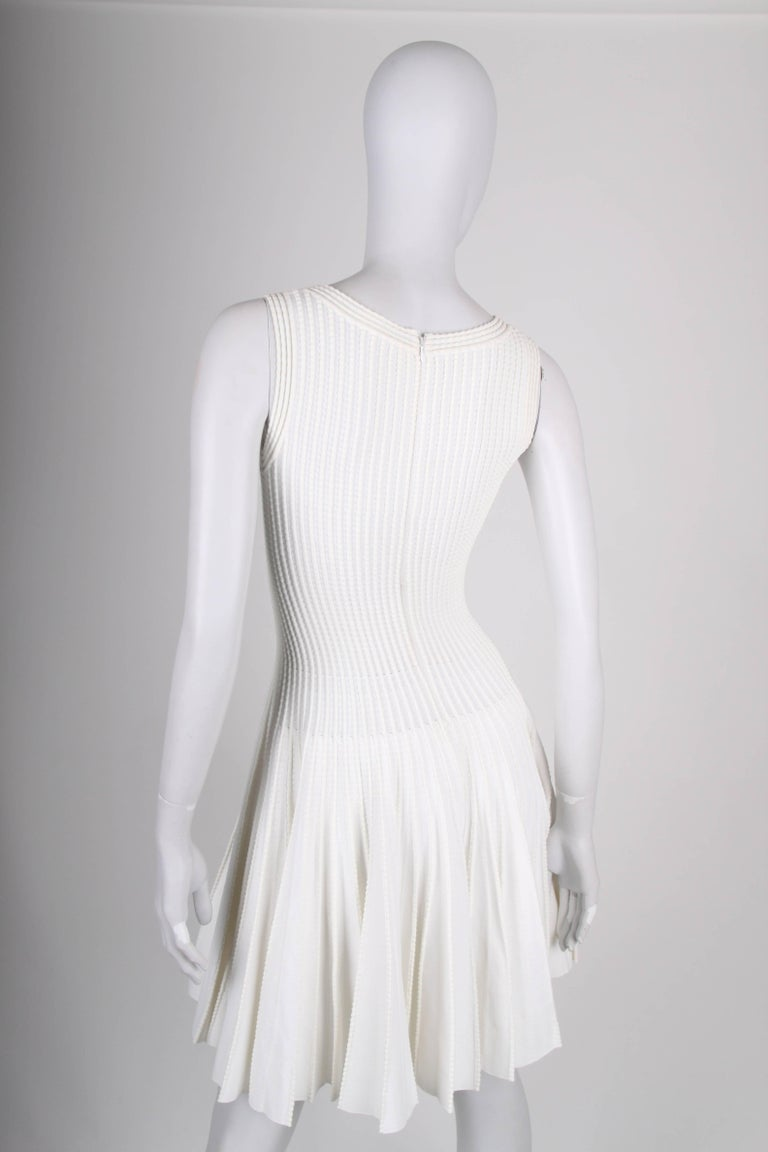 This is a stunning beauty by ALAIA!  Sleeveless dress with a long zipper on the back. Round neckline and a wide pleated skirt. Very comfortable to wear due to the stretching material.  In very good condition, 9/10  Material: 50% viscose, 30% cotton,