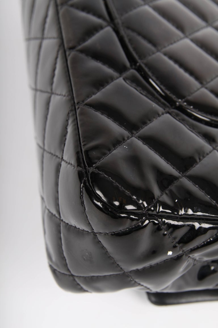 Classic bag by Chanel in black patent leather, this is something else!   This 2.55 medium double flap bag is the middle size of this classic model and measures 26 centimeters in length and is 16 centimeters high. A silver-tone chain which can be