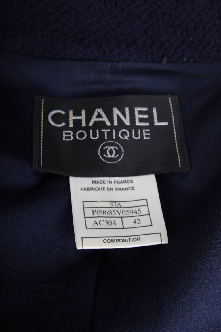 Neat two-piece suit by Chanel in dark blue boucle wool. We like!  The jacket has a rather large collar and front closure with a blackish silver zipper. Around the zipper some embroidery has been applied in red, green, yellow and blue. Two welt