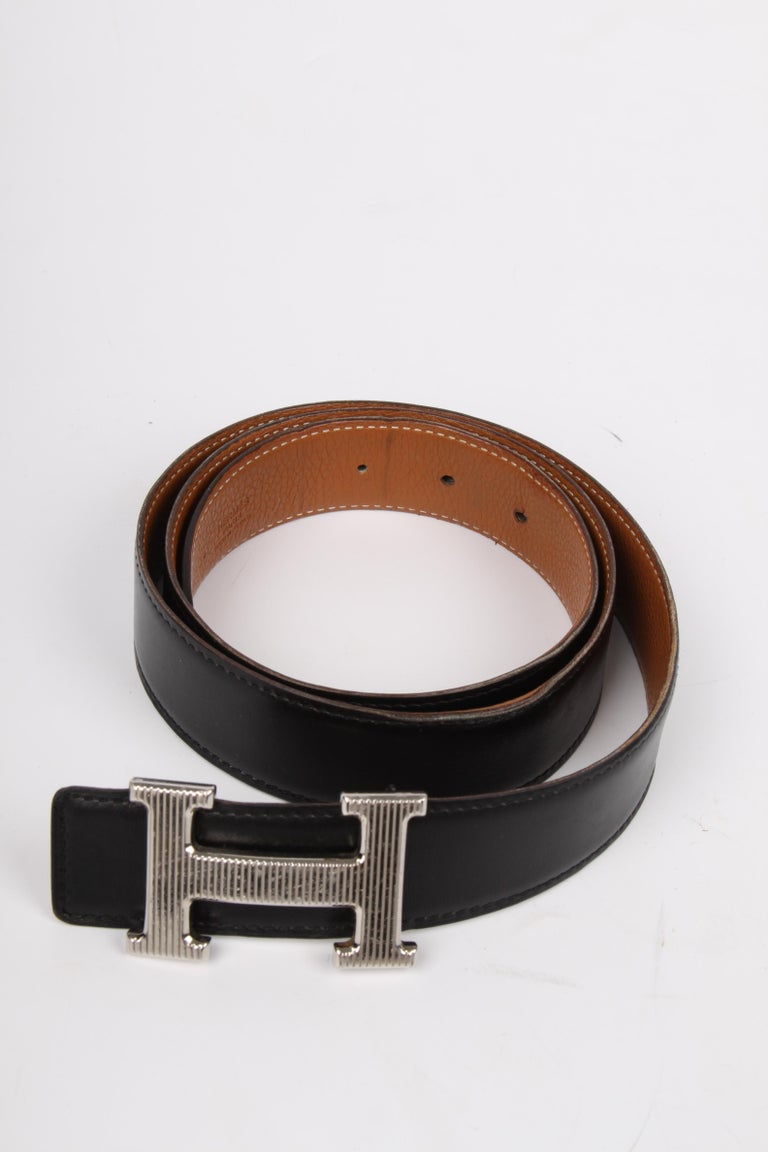 The welknown 'H' belt by Hermès, this one is reversible!  One side is crafted from black leather, the other side is brown. Length of the belt is 95 centimeters, 3 centimeters wide, embossed with stamp L. The silver-tone H buckle has vertical stripes