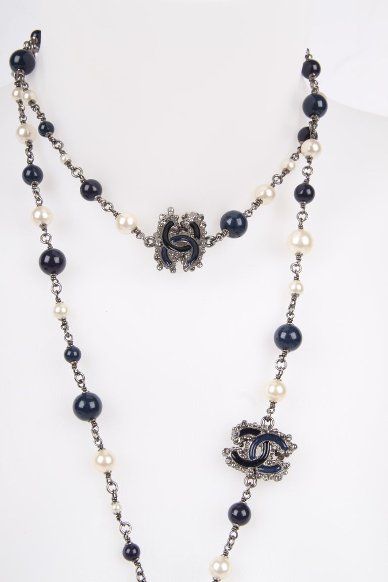 Endlessly long necklace by Chanel. Neat!  This blackish silver necklace measures as much as 160 centimeters. Dark blue beads and softly shine white faux pearls in different sizes alternate one another.  Three dark blue enamel CC logos with small