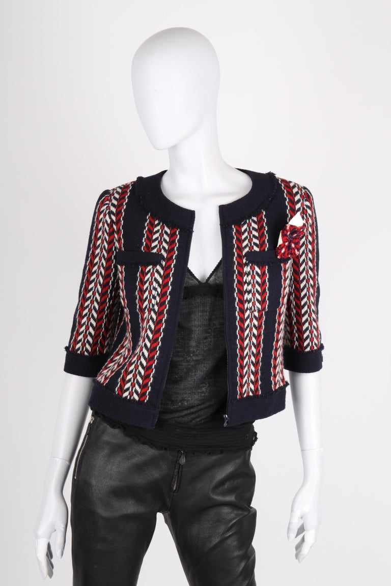 Marvellous Chanel coat in dark blue, red and white wool from the fall collection of 2004.  A round neckline, patch pockets at the chest, short sleeves and a zipper at the front. A flower brooch on the left, which can be removed.  Short model, fully