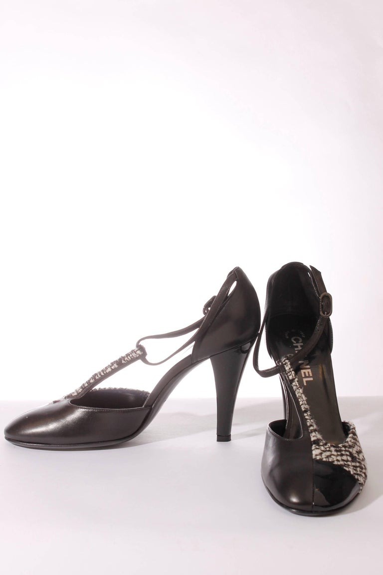 Sophisticated shoes by Chanel in leather, patent leather and tweed.  A small leather strap around the ankle, the patent leather heel measures 10 centimeters. On the front and the vertical strap some black and white tweed is used. A round toe.