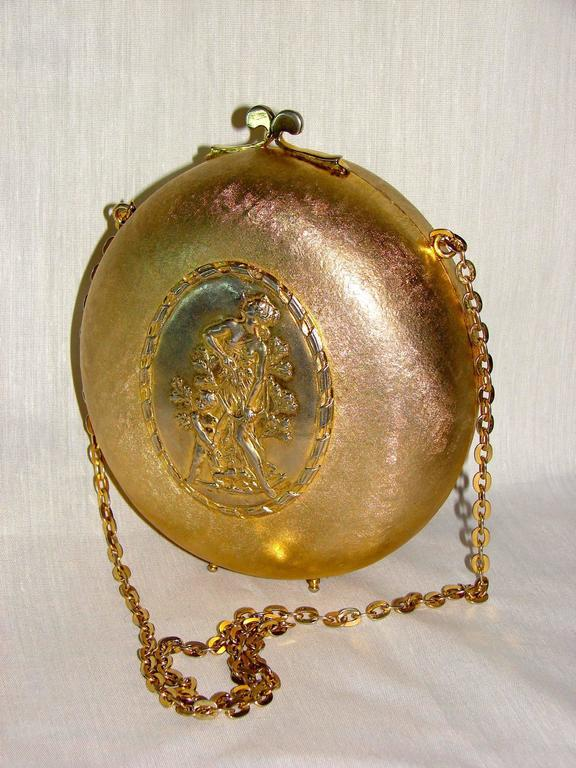 A gilt metal evening bag attributed to Rosenfeld circa 1965.  Made from a gilt exterior, it features a center plate in silver with neoclassical style figures.  Inside is lined in gold velvet and still retains its 'Made in Italy' tag.