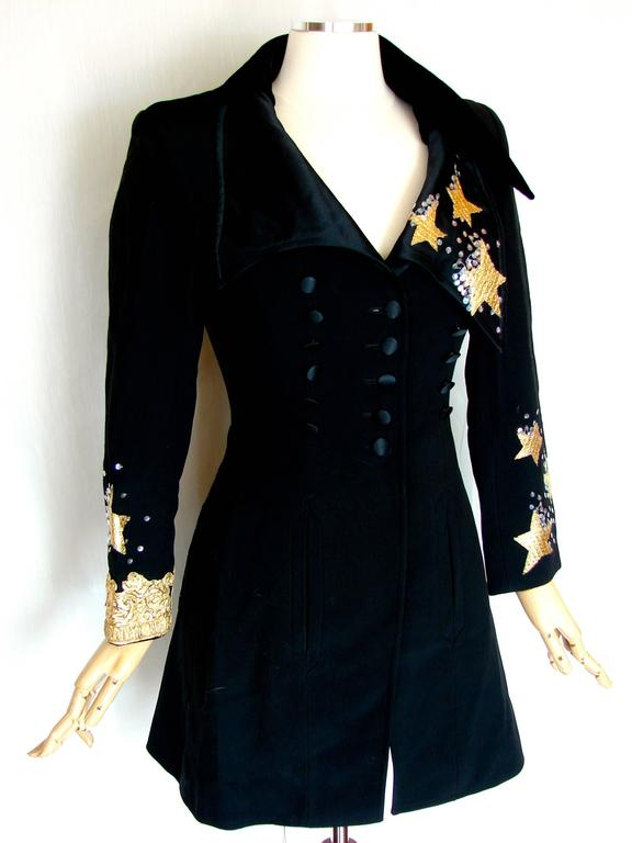 This fabulous long jacket was designed by Christian LaCroix in the 1980s.  Made from a viscose blend fabric, the large lapel collar is made from black velvet and features snakeskin embroidery stars, gold embroidery trim and dots of sequins.  The