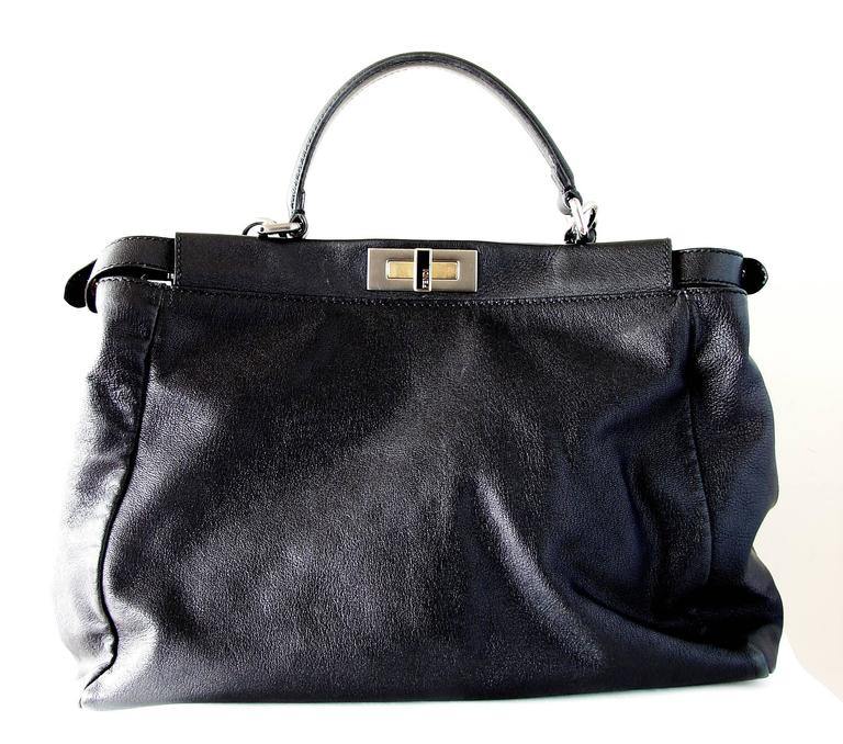 This incredible black leather handbag is from Fendi and features their stylish peekaboo design.  This substantial bag features two large sections, both lined in Fendi Zucca fabric, and features both gold and silver hardware throughout. It comes with