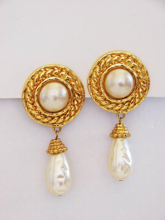 An incredible pair of earrings from Edouard Rambaud circa the late 1970s.  Made from gold metal, these feature large faux pearl centers and Baroque style faux pearl dangles.  Measure 2.75in L and stamped Edouard Rambaud.  In excellent condition,