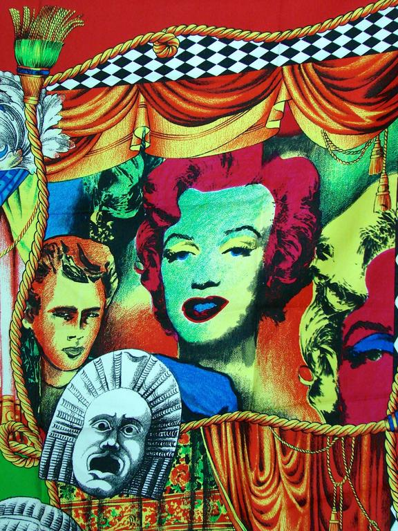 Here's a piece for the true Gianni Versace collector. This rare silk twill scarf features Versace's iconic images of Marilyn Monroe and James Dean as well as several Roman motifs against a vibrant red background.  Made from 100% silk, it measures 35