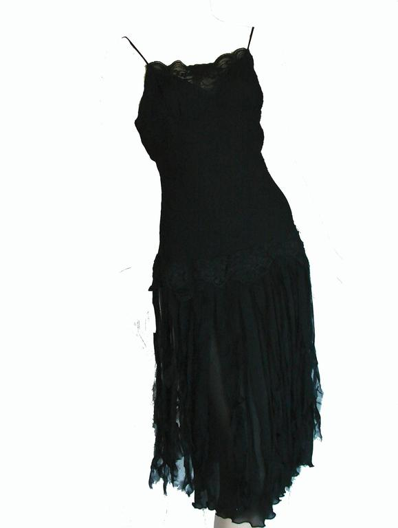Here's a pretty little slip dress by Betsey Johnson.  Made from black silk and lined in polyester, it features lace trim at the chest and unfinished car wash strips of silk on the skirt.  Tagged size 6, it measures, taken flat and doubled where