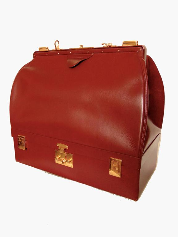 This rare Sac Mallette bag or travel case was made by Hermes, most likely in the 1970s.  Made from their classic box leather in a rich shade of cordovan, this piece features two compartments: the top section, which is tall and lined in goat skin for