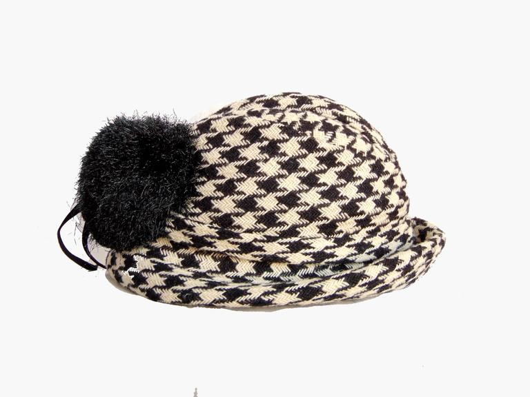 Here's a lovely fedora hat and scarf ensemble from Adolfo. Made from a black & white houndstooth knit, the hat features a black pom pom in back and the scarf is fringed.  The hat measures 22.25