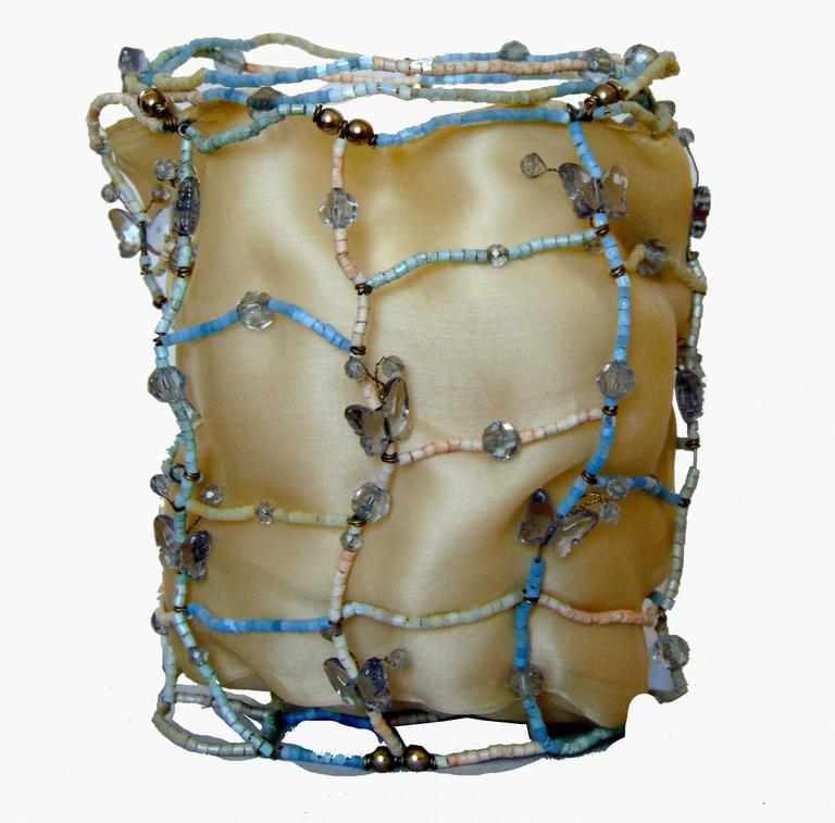 Hard to find bag from Bottega Veneta.  Made with a wire frame covered in pale powder blue and white beads, it features gemstones and tiny butterflies throughout.  Fully lined in cram silk, it has two dainty wrap ties at top.  Stamped Bottega Veneta