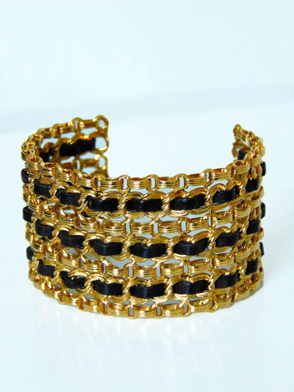 This fabulous wide cuff bracelet was made by Chanel, likely in the early 1980s, Made from gold metal chains, it features black leather strips interwoven throughout.  In excellent condition.  It measures appx 2.75in diameter x 2in H.  Stamped CHANEL.