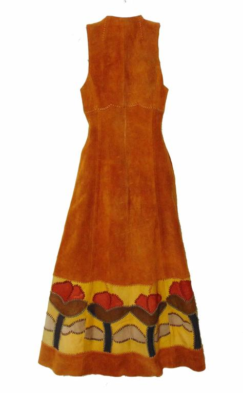 This unusual long festival dress or vest was designed by Char, Charlotte Blankenship de Vasquez, in the early 1970s.  Made from tan suede leather, it features whip stitching and leather floral inserts at the bottom hem and waist ties. So chic - it