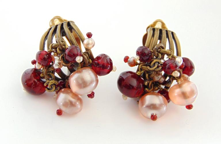 These glass bead torsade earrings were made by Chanel for their 00A collection.  They feature poured glass beads in shades of ruby red and translucent white, with teensy brass metal CC charms throughout.  Very chic! Measurements:1.25in long  x 1in
