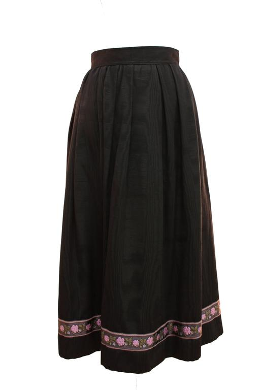 This incredible black moire silk skirt was designed by Yves Saint Laurent circa 1976. It's constructed with a high waistband and full skirt, and features an embroidered floral motif at the hem and hidden side pockets.  In excellent condition for its