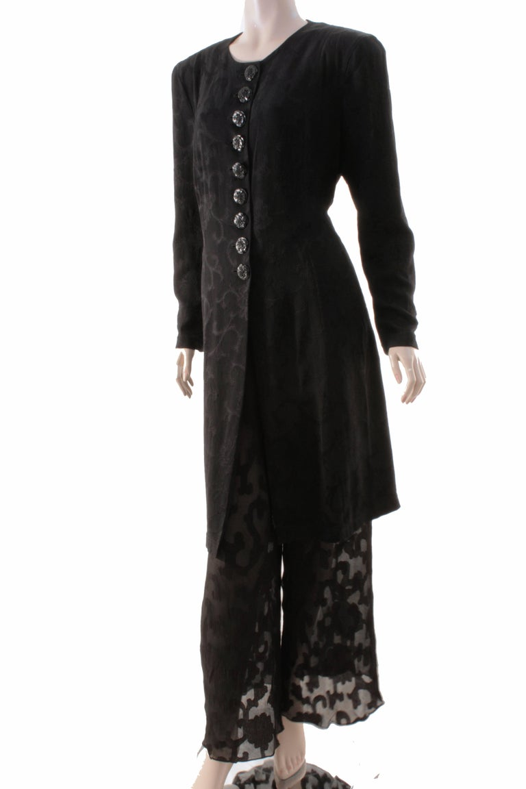 Here's a chic two-piece jacket and pants set from Donna Karan, and sold by high end luxury retail center LEONE in BC.   Made from black silk, the jacket features a floral brocade pattern throughout with a row of floral shaped buttons to fasten. The