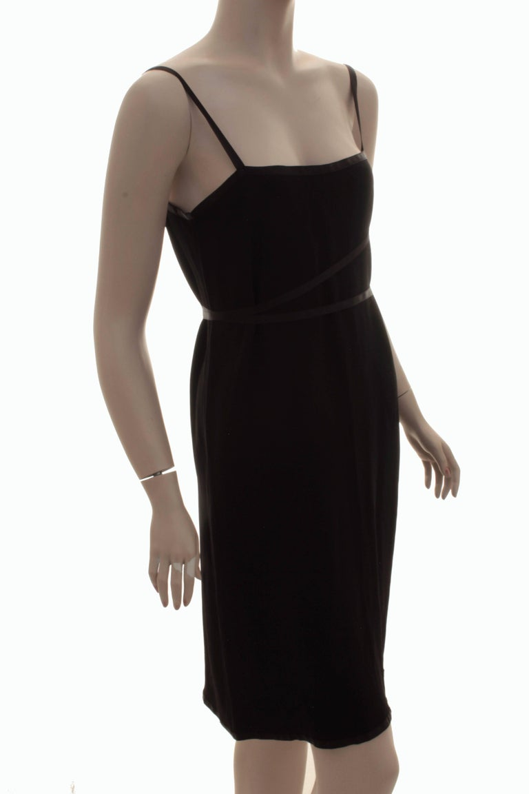 This chic black cocktail dress was made by Yves Saint Laurent Rive Gauche, most likely in the late 1970s, early 80s.  Made from a black crepe fabric, its trimmed in black silk satin at the chest and skirt hem, and has two long satin ribbon ties at