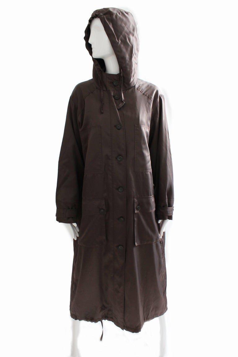This chic trench coat was made by Sonia Rykiel, most likely in the early 1990s.  Made from a deep brown satin, it features an attached hood, zippered front with button overlay, and large button square pockets at each hip.  The bottom hem features a