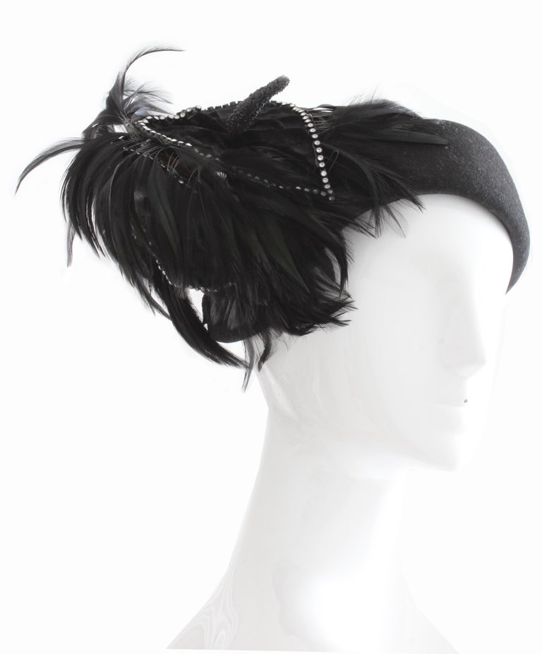 This gorgeous black wool hat with feathers was made by Bollman Hat Co and Jack McConnell, most likely in the early 60s.  Made from black wool, this piece features a decorative velvet covered floral piece that's outlined in rhinestones with