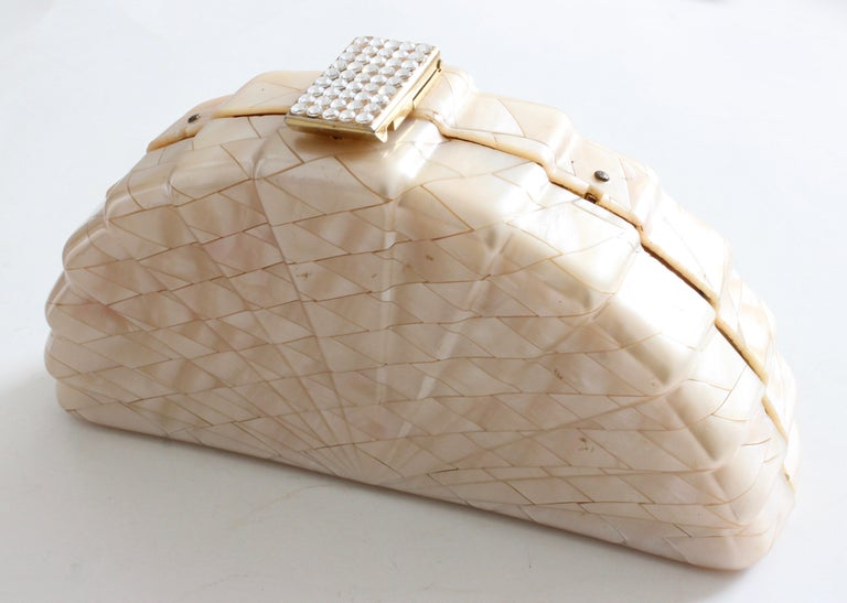 This fabulous little bag was made in Italy for Saks Fifth Avenue, most likely in the early 1960s.  Made from what appears to be highly polished shells in a modern mosaic pattern, this bag fastens with a rhinestone-encrusted latch and features a gold