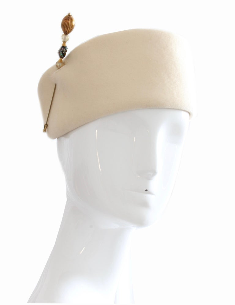 Here's an early pillbox hat from Halston, who started off making his own hats in the 1950s, before being known for his clothing in the 1970s.  Made from a vanilla wool, this hat features a beaded stick pin, which makes it look so elegant.  In good