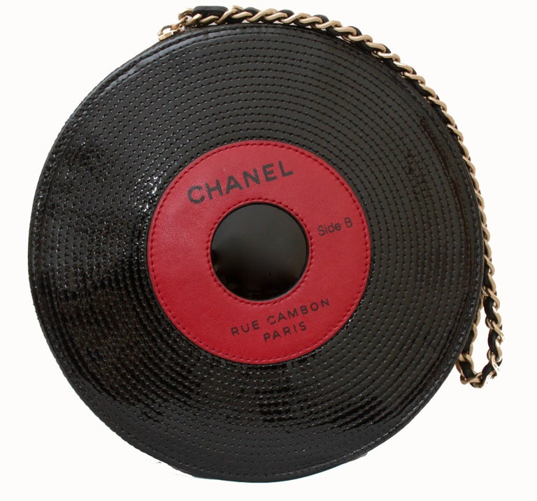 Here's a whimsical clutch bag from Chanel's Spring 2004 collection. Made from stitched patent leather, it features a red leather center, black leather and brass chain carry strap and fully-lined fabric interior. Fastens via zipper. In excellent