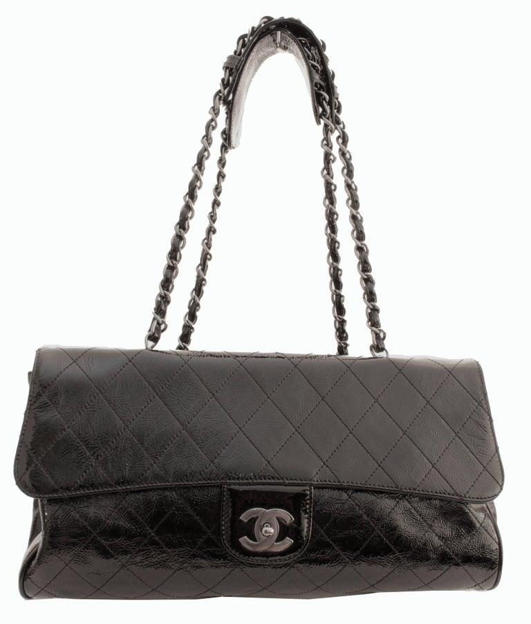 This Chanel Ritz bag was produced in 2005 and is made from black patent leather in their signature Matelasse quilted diamond motif.  It features removable silver chains with patent shoulder straps so that one can carry either on the shoulder or as a
