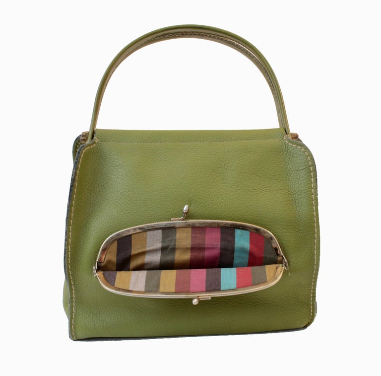 This rare bag was designed by Bonnie Cashin during her time at Coach Leatherware in the 1960s.  Made from an eye-popping lime green leather, it features a large brass kiss lock coin purse in front, and double leather covered handles.  Inside is