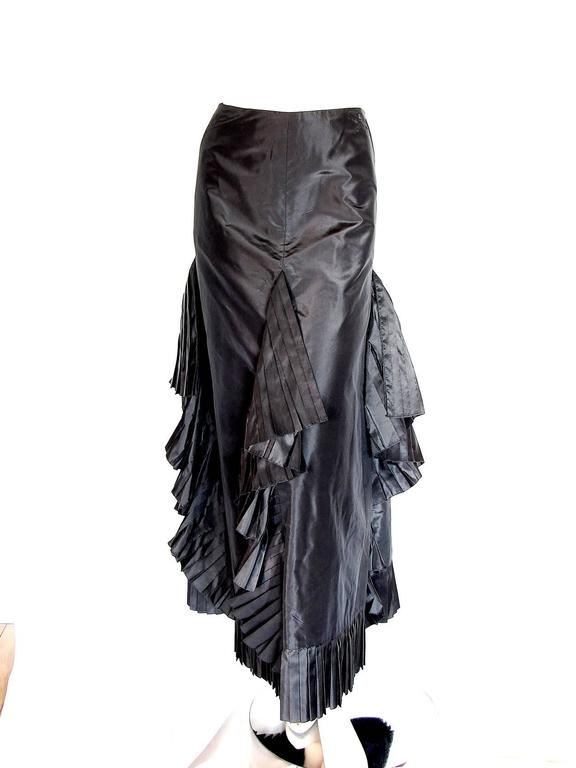 This incredible silk taffeta skirt is constructed with panels of pleated ruffle fabric, fitted at the waist and hips, and features an asymmetric hem.  One flat pocket can be found at each hip, and there is one rhinestone-encrusted CC on the left