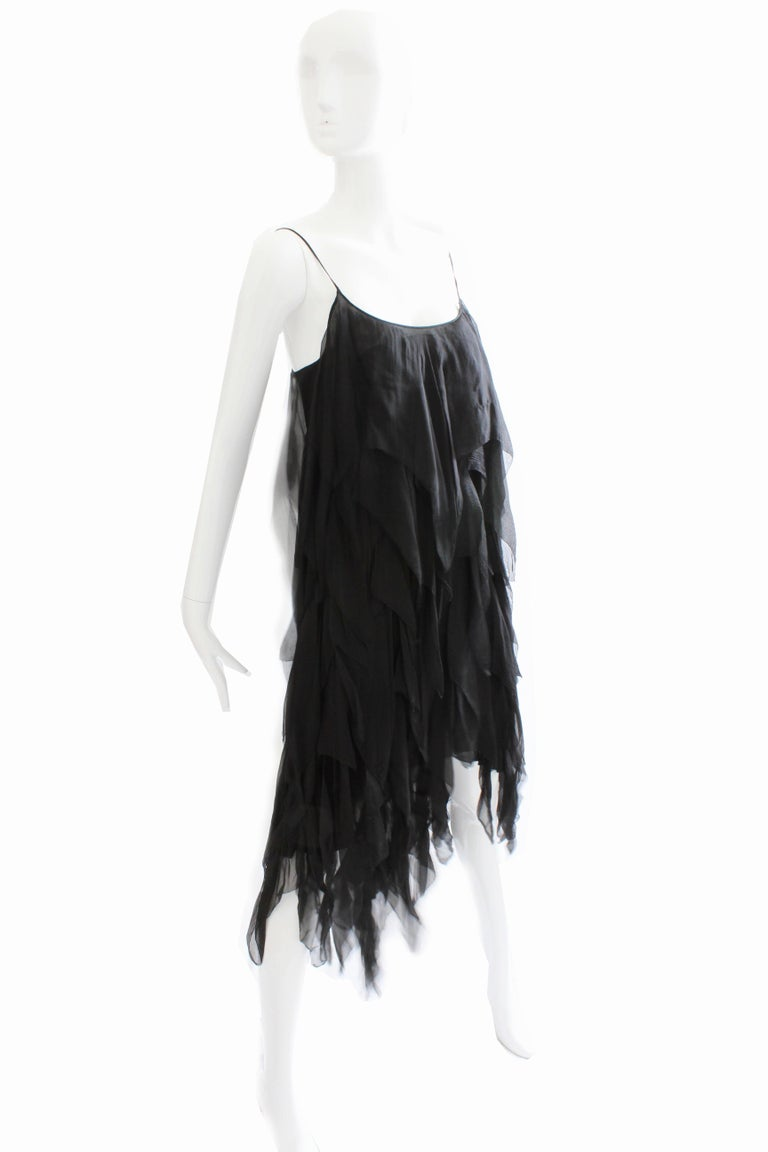 This little black dress was designed during the mid 1970s, after Gabrielle 'Coco' Chanel passed away and before Karl Lagerfeld was brought in.  It's made from tons of tiered sheer black silk panels that daintily swish as you walk, and features an
