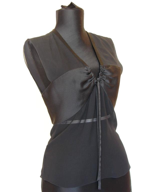 This sheer blouse by Chanel made from silk and features satin side panels at the bust with cinching, and fastens in back with Chanel-stamped buttons and a hook/eye fastener.  In excellent pre-owned condition with no issues to report. Tagged CHANEL