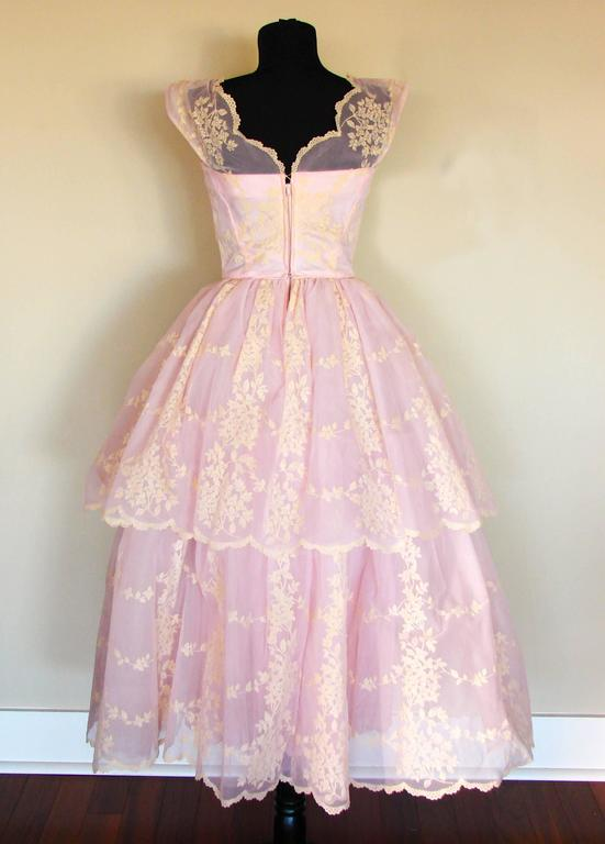 This adorable vintage dress is so cheerful! Made from baby pink satin taffeta fabric, it has layers of tulle on the underskirt and a sheer panel with dainty floral motif on top. We love the unusual tiered skirt! In very good condition overall, we