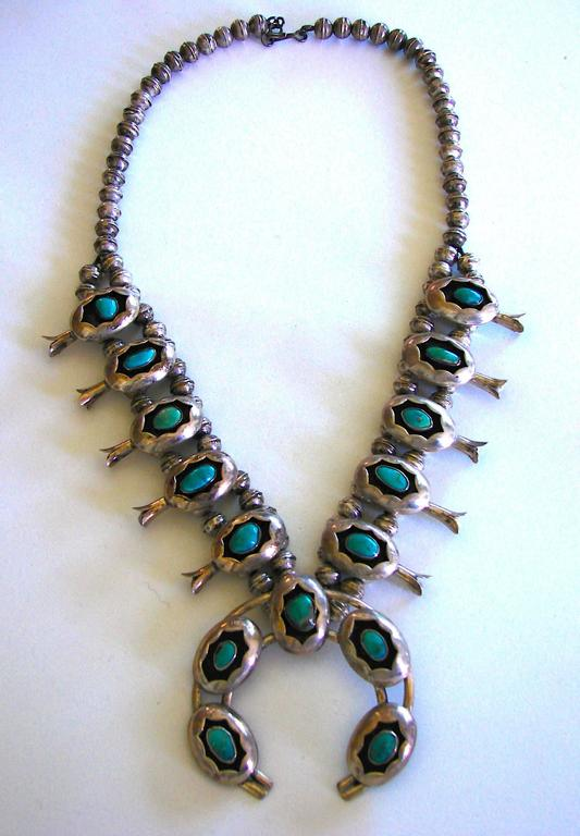 Massive vintage necklace from the 1970s features sterling silver and turquoise.  The necklace is about 23in long without the naja. The naja is about 2.5in diameter.   Unmarked.  In excellent condition with some tarnish to the silver, most notable on