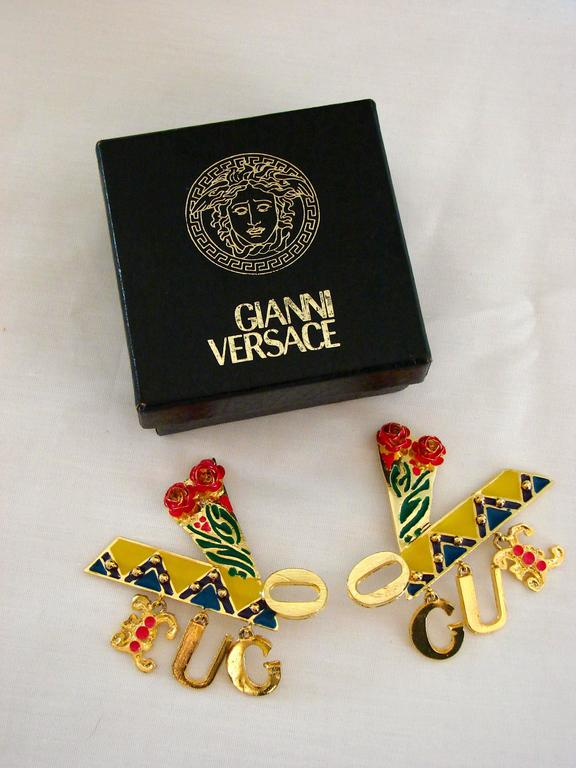 Massive gold earrings from Gianni Versace c1990 feature colorful enamel and rose details, and spell out the word 'Vogue' with dangling charm letters (very similar to the reboot version Donatella released at Milan Fashion week, sported by Kaia