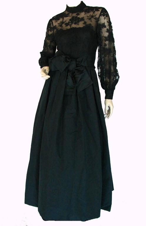 This black lace and taffeta evening gown was made by Ronald Amey in the 1970s and is absolutely gorgeous.  The bodice features black floral lace with netting underneath, and the the darted skirt is made from what appears to be a black silk taffeta
