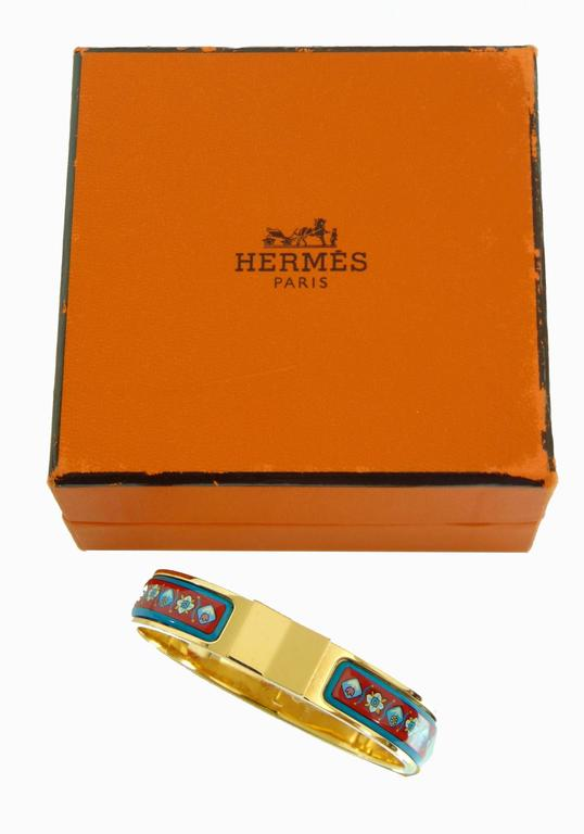 This gold Hermes Clic Clac bracelet is from their 2006 collection and is hard to find in this red and blue floral color way.  In excellent condition for its age, we note scratching to the gold hardware from prior wear.  Comes with box (box shows