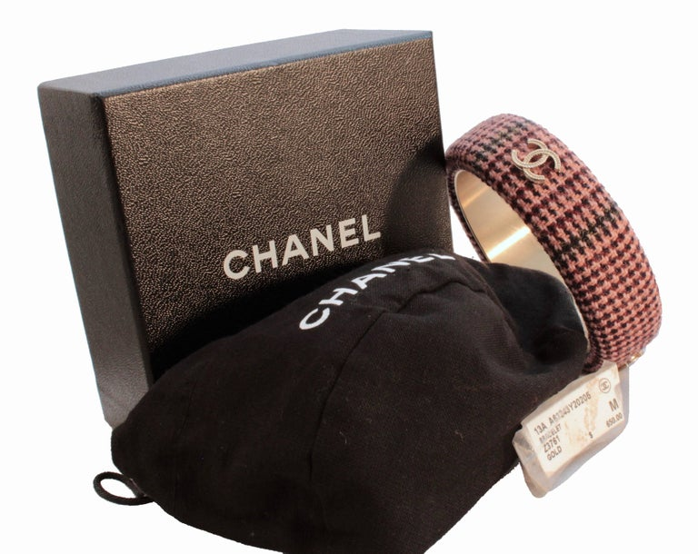 Here's a fabulous bangle bracelet from Chanel's 13A collection.  Made from a pink tweed, it features gold Chanel CC logos.  This piece is new in box, however there are very minor surface scratches to the inside gold metal from being tried on while