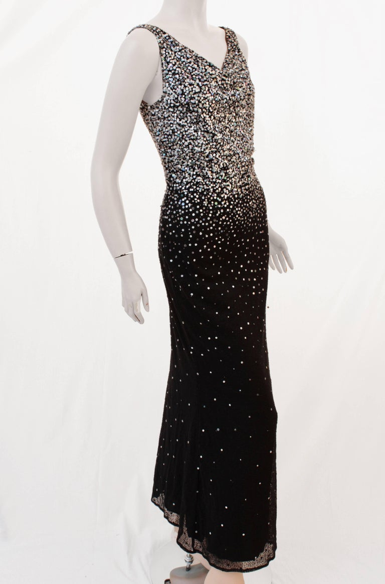 This fabulous form fitting evening gown was made by Naeem Khan and sold by luxury boutique Barbara Katz of Boca Raton, most likely in early 2000.  Made from black silk, this full-length gown features hundreds of sequins that shimmer and throw off