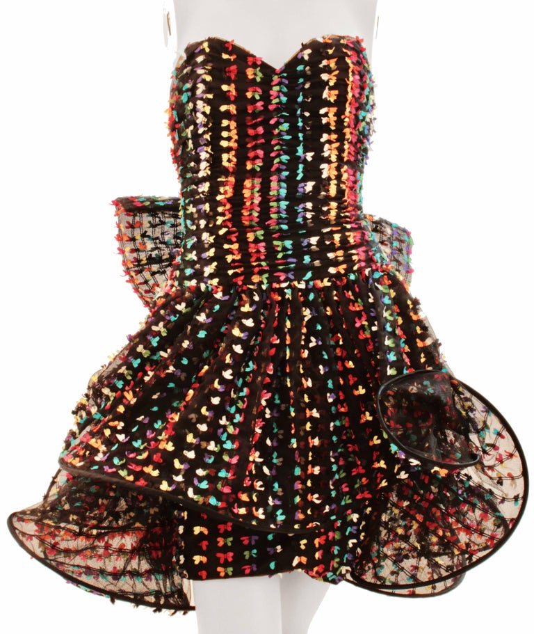 This little cocktail dress was made by London designer Tomasz Starzewski, likely in the late 1990s.  Made from a black cotton blend mesh fabric, it features dozens of tiny confetti colored bows with a pliable hooped layer overlay at the skirt.