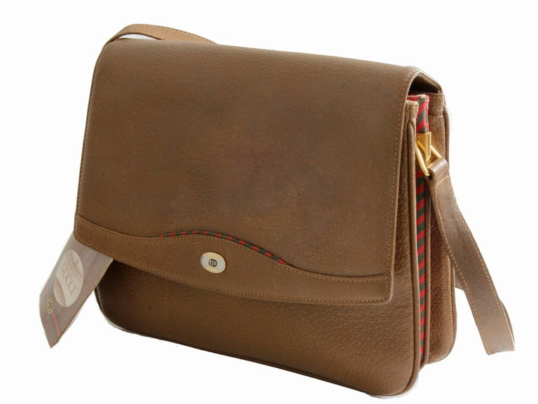 This leather shoulder bag or messenger was made by Gucci for their Accessories Collection, most likely in the early 1980s.  Made from their pigskin leather in brown, it features green and red coated leather accents at the bag bottom, sides and top