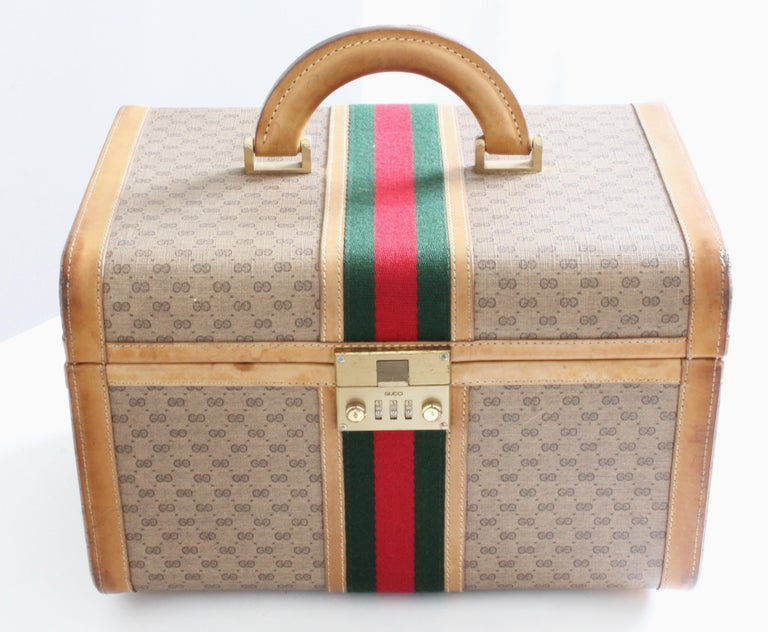 This fabulous vintage train case was made by Gucci, most likely in the early 1980s.  Made from their small GG logo canvas, it's trimmed in light saddle leather and features Gucci's iconic webbing at the center.  Fastens with a combination lock (set