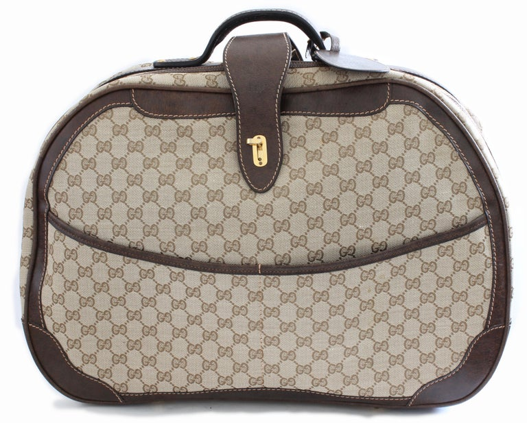 This rare carry on bag was made by Gucci, most likely in the 1970s.  Made from their Gucci GG logo canvas and trimmed in brown leather, it features a rolled leather top handle, dual zippers and seven golden feet on the bag bottom,  The interior is