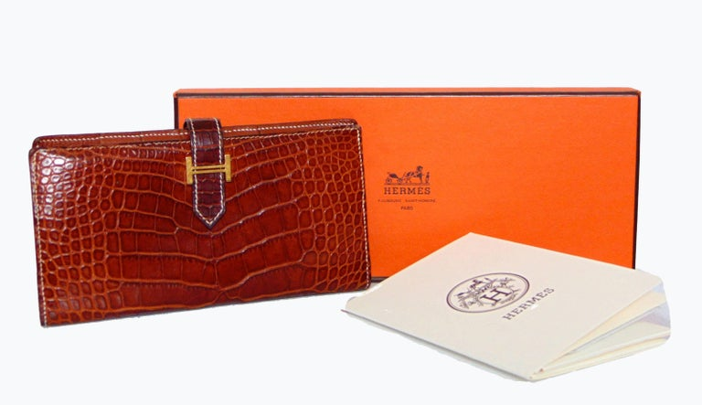 This incredible wallet was made by Hermes in 2004.  Made from their signature alligator skins in a rich honey or Miel color, this wallet features white contrast stitching and fastens with a gusset.  The interior is lined in matching honey goatskin.