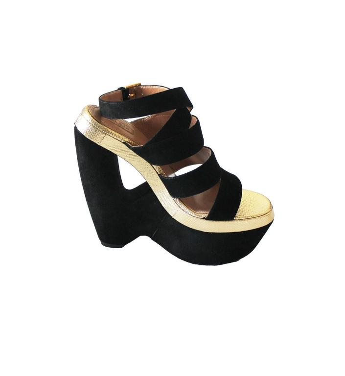 An AZZEDINE ALAIA classic signature piece that will last you for years This gorgeous pair of wedges made out of finest black suede with cut-out wedge heel Accented with real beautiful golden lizard leather Golden closure discreetly engraved with