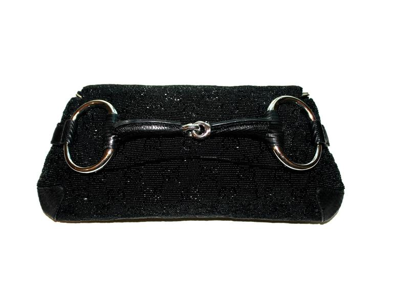 A Gucci signature piece in the famous GG Monogram  Beautiful beaded jet black bag with lizard skin trimmings Famous Gucci signature horsebit design White-gold colored hardware Detachable strap discreedly engraved with
