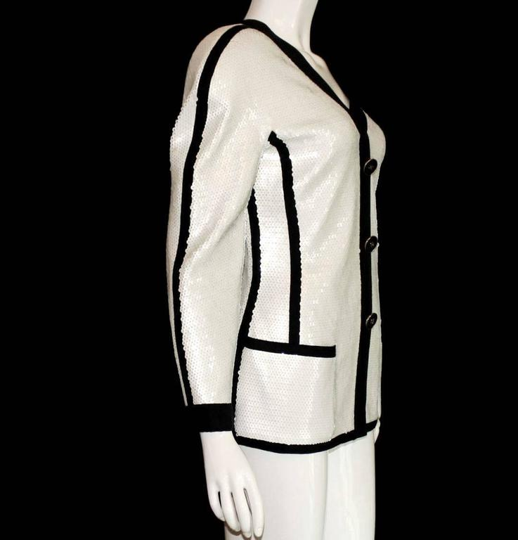 An extremely rare Chanel jacket from the early 1990s Seen on Vogue Editor Anna Wintour Part of the Exhibition in the Metropolitan Museum in NY in 2005 White Sequin Jacket with black trimming Closes with a hidden zip in front Decorative black CC