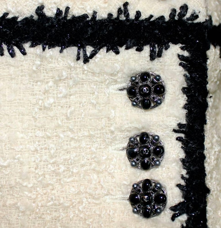 Beautiful CHANEL skirt designed by Karl Lagerfeld A true CHANEL signature item in the so famous black and white that will last you for many years Faux wrap skirt with Chanel CC jewelry buttons Completely lined with finest stretchy silk Beautiful