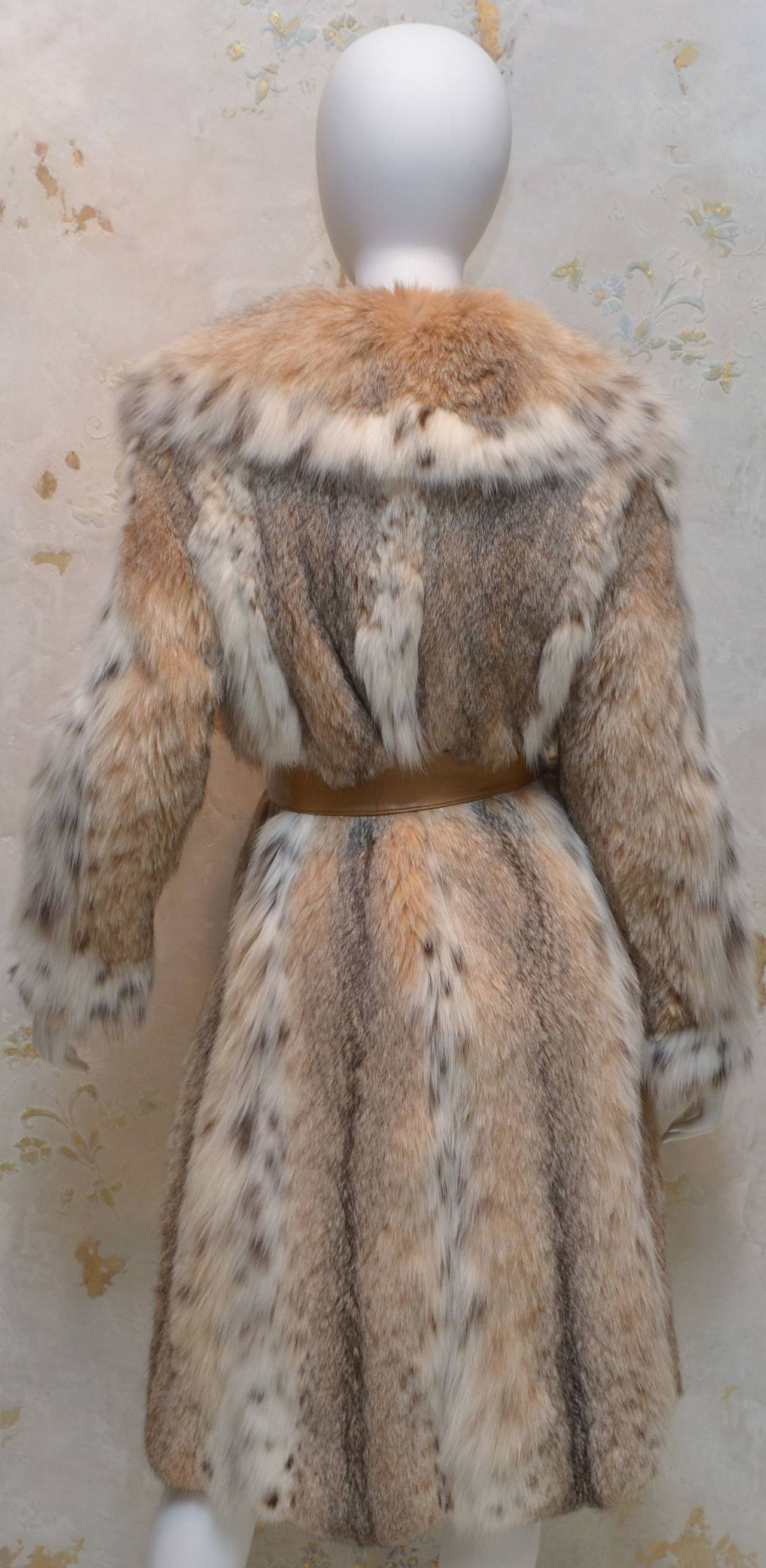 1960's Lynx coat features a spotted detail throughout, leather waist tie, fully lined coat, and pockets at the hips. Coat is in excellent condition!  Measurements: Bust - 34'' Waist - 30'' Sleeves - 22'' Length - 43''